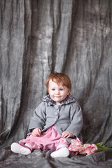 Little girl wearing autumn grey coat, over gray background