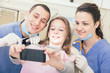 Happy patient, dentist and assistant taking selfie all together