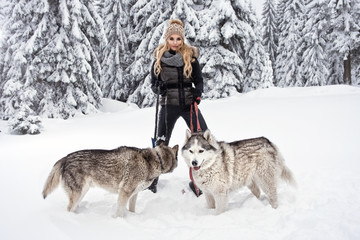 Happy young woman playing with husky dogs