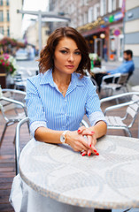 Woman in blue blouse at a cafe.