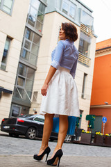 Woman in white skirt and blue blouse.