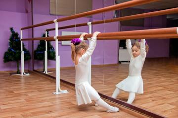 Ballet dancer little girl in class on the handrail