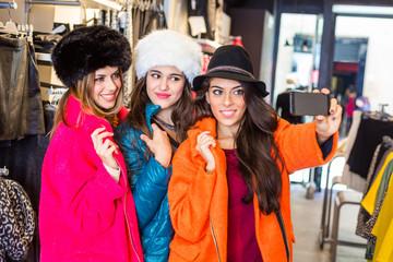 Three women taking a selfie wearing colorful coats