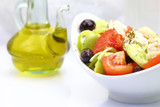 Bowl with fresh salad and olive oil on tabletop