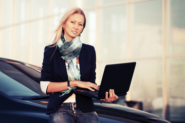 Young fashion business woman with laptop on the car parking