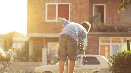 Durstiger Junge trinkt Hahnenwasser