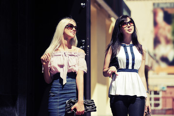 Two young fashion women walking on the city street