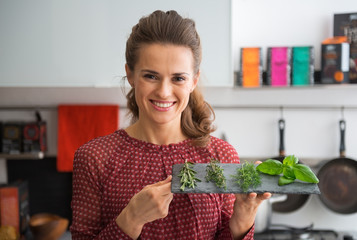 Portrait of happy young housewife showing fresh spices herbs