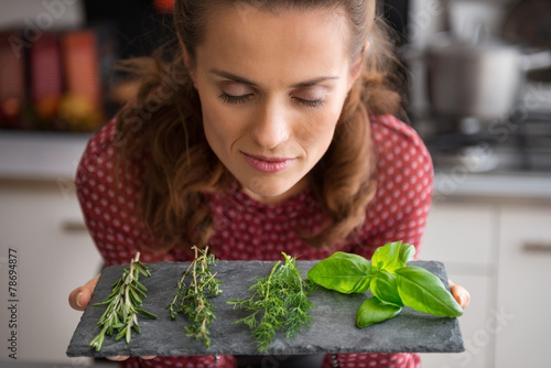Fototapeta Portrait of young housewife enjoying fresh spices herbs