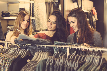 Three women in a clothing store choosing a dress