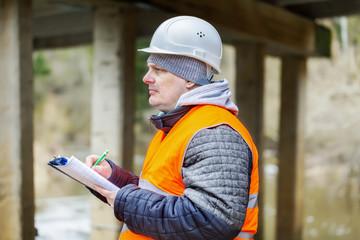 Engineer with  documentation under the bridge