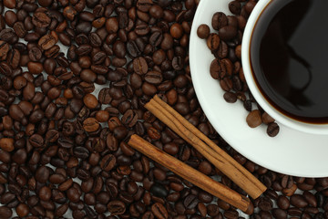 Cup with coffee on plate on coffee beans background