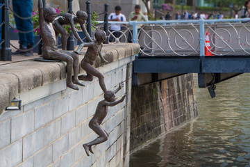 Bronze statues of kids jumping into river