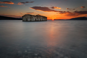 A sunset view of the sunken ruins of an abandoned church