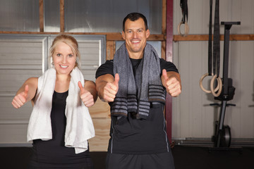 Cross fit - thumbs up couple in a gym
