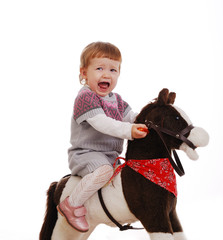 Little girl  on her first toy horse isolated on a white