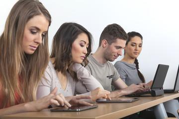 Studenten arbeiten mit Tabletts und Notebooks