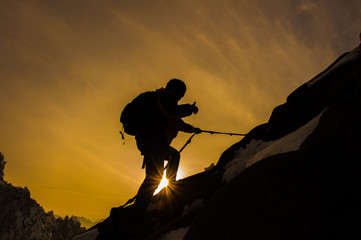 Silhouette of mountaineer and sunset.