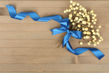 Decorative  flower branch with a ribbon on a wooden background