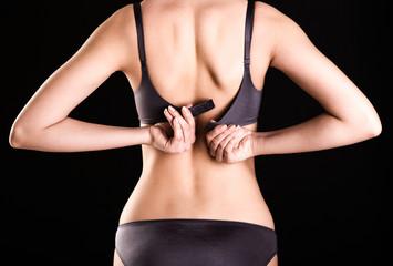 Back view portrait of a woman unbuttons her bra