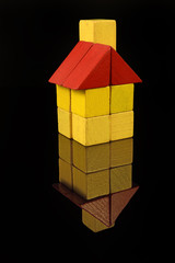 House of wooden blocks, traditional toy on black background