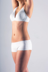 Slim woman's body over gray background