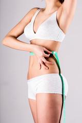 Slim woman measuring waist with tape measure