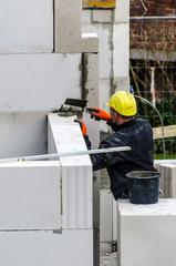 Maurer mauert Wand auf Baustelle