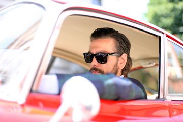 Mann mit Bart und Sonnenbrille im Oldtimer