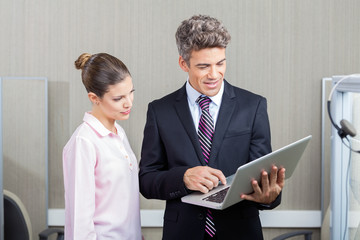 Businessman And Call Center Employee Using Laptop