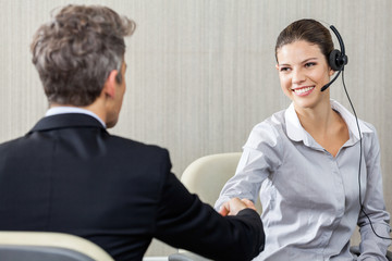 Young Female Customer Service Representative Shaking Hands With