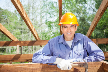 Smiling Male Worker Holding Hammer At Site