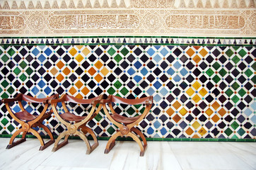 Chairs and the wall of tiles in The Alhambra, Granada, Spain
