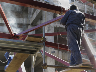 Welder with protective helmet welding metal on construction site