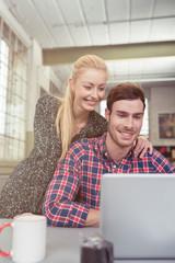 junges paar schaut zusammen auf einen laptop