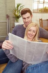 junges paar liest die tageszeitung
