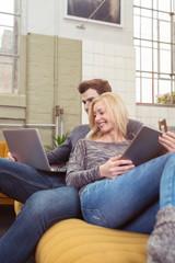 entspanntes paar mit laptop und tablet-pc