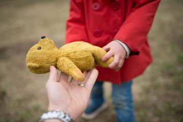 熊の縫い包みを手渡す親子の手