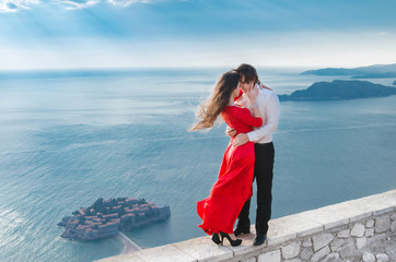 Romantic embracing couple beside blue sea in front of Sveti Stef