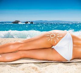 Hot beautiful woman in bikini lying on the beach.