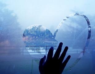 hand drawing heart on wet window