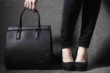 Fashionable woman in heels with bag
