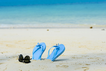 blue slippers and sunglass on the beach