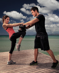 Man and woman doing fitness at beach: fight exercises