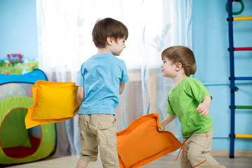 Two children playing with pillows