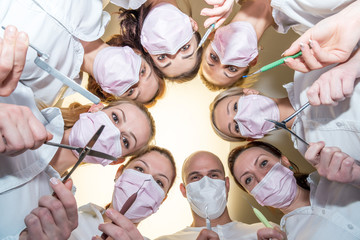 A team of dentists with tools and masks bending over patient