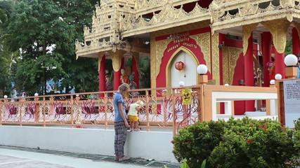 little blonde child climbs barrier near Buddha temple