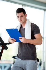 trainer with clipboard standing in a bright gym