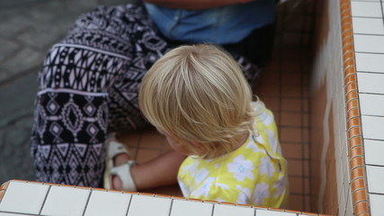 Little blonde child sits by her mother on bench on