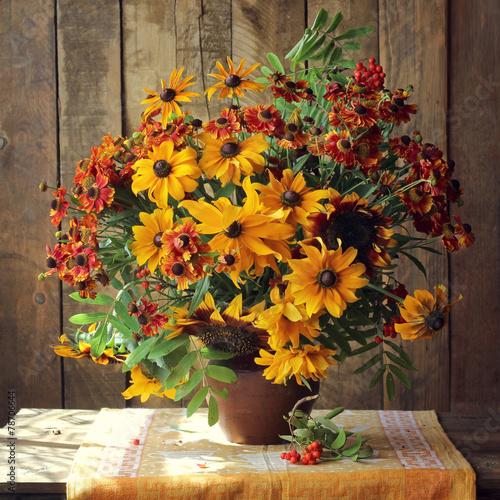букет из красных и желтых цветов на фоне досок